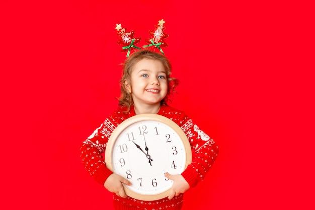 Ребенок маленькая девочка в зимней одежде держит часы на красном фоне. новогодняя концепция, место для текста