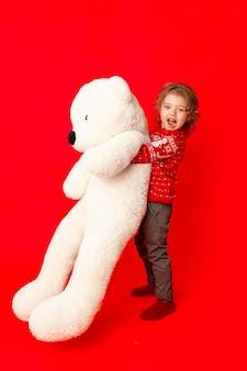Ребенок маленькая девочка с большим плюшевым мишкой в зимней одежде на красном фоне, место для текста