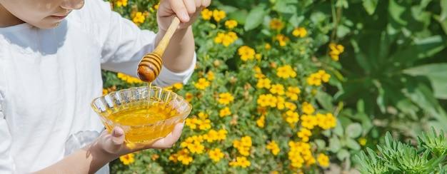 子供の手に蜂蜜のプレート。セレクティブフォーカス。