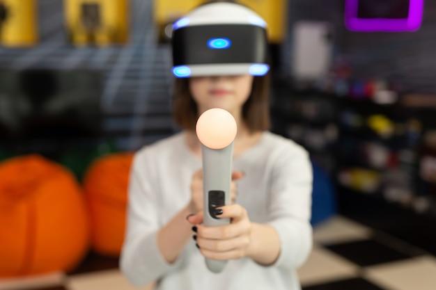 10 代の少女、ゲーム クラブでリモート コントロール銃でゲームを撮影する仮想現実のメガネでゲーム コンソールで遊んでいます。 vr