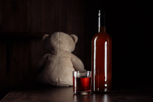Child abuse concept. teddy bear as a symbol of child's safety and bottle with glass in a dark room.
