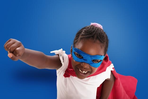 子供は青い背景で世界を救うためにスーパーヒーローのように振る舞います