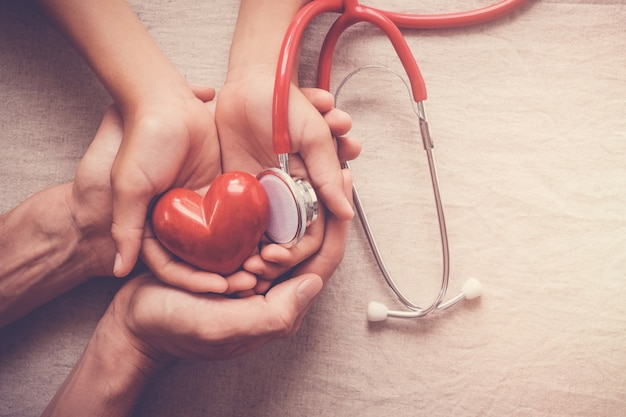 Child and adult holding red heart with stethoscope, heart health,  health insurance concep