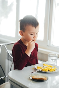 A child in the afternoon on a white light kitchen in a burgundy sweater eats an omelet