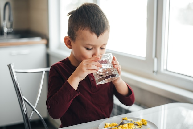 A child in the afternoon in a white light kitchen drinks water from a glass