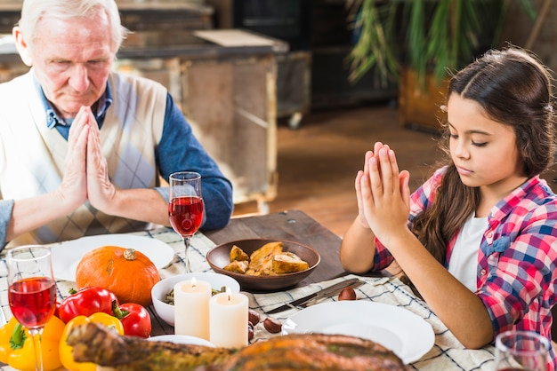 Child and aged man praying at table