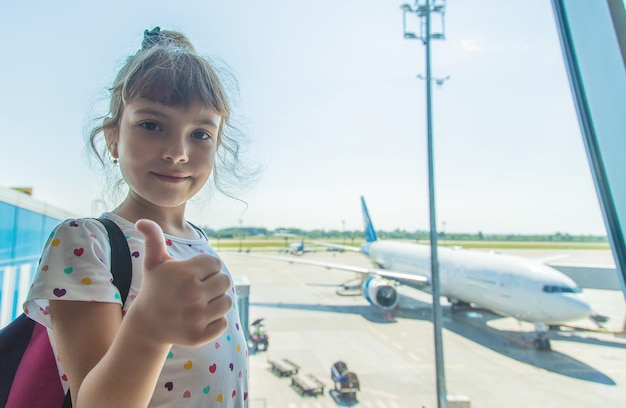 A child at the airport on the background of the aircraft