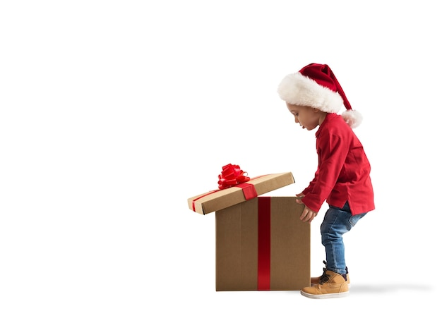 大きな魔法のクリスマスプレゼントに驚いた子供。白色の背景