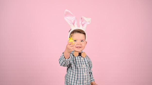 Ребенок и пасха, на розовом фоне. фото высокого качества