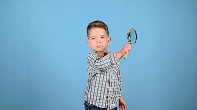 青い背景に子供と虫眼鏡。高品質の写真