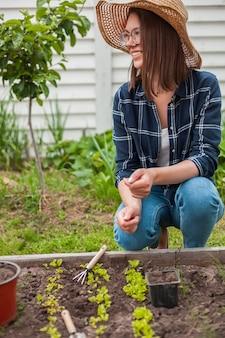 뒤뜰의 채소밭에서 가꾸는 아이와 어머니