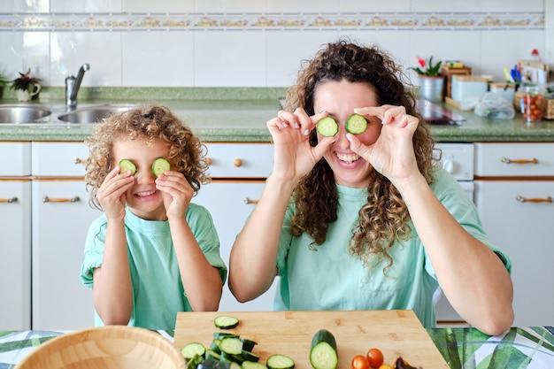 子供と母親は、食事の準備をしながら、2つのキュウリのスライスを目に入れてキッチンで遊んでいます