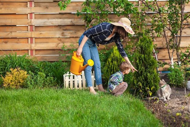 뒤뜰에 있는 정원에 물을 주는 어린이와 어머니