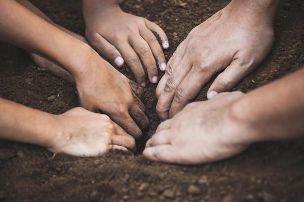 토양을 파고있는 어린이와 부모는 나무를 함께 심을 준비를합니다.