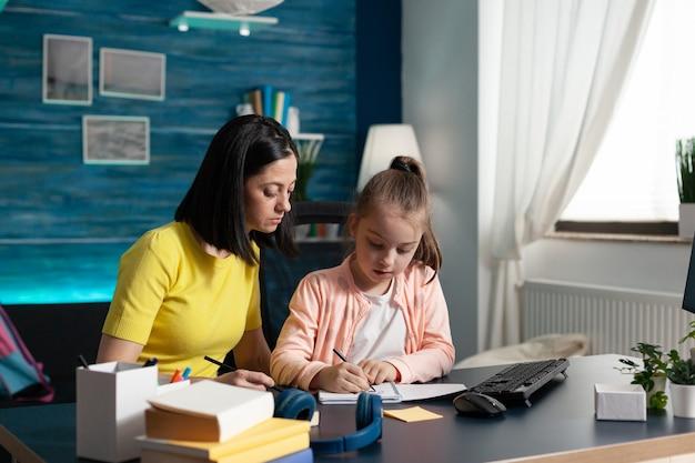 Ребенок и родитель вместе делают домашнее задание дома