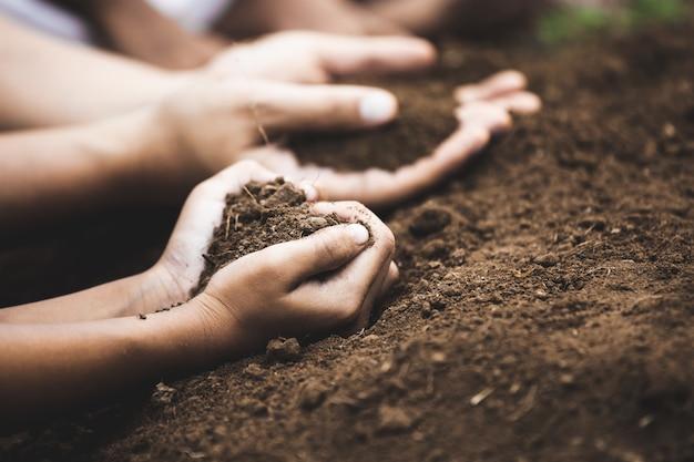 심장 모양의 토양을 잡고있는 어린이와 부모는 심기를 준비합니다.