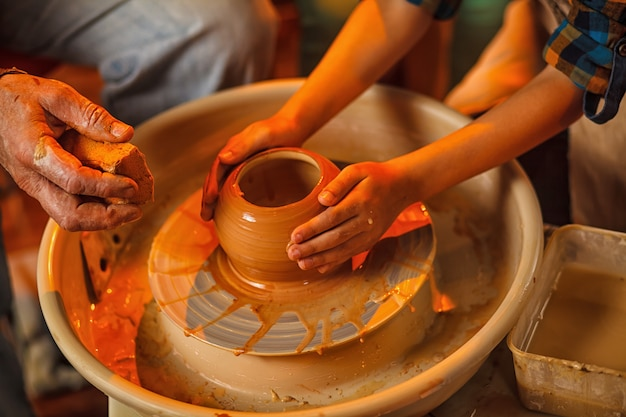 Child of the art of making a pot or a vase of clay.
