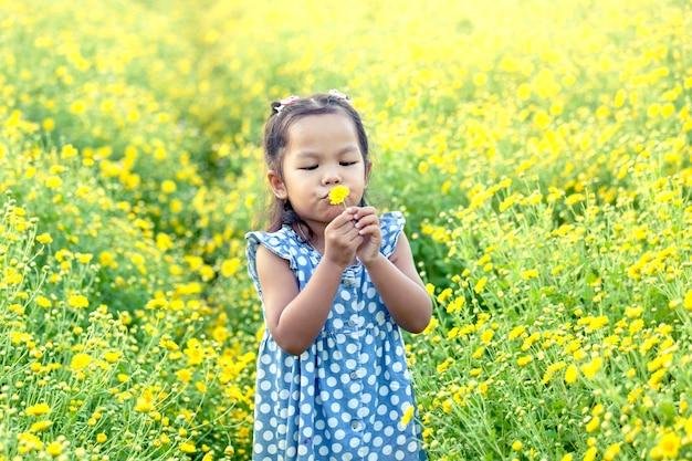Ребенка азии девочка, дует желтый цветок в саду, с удовольствием с желтым полем цветов