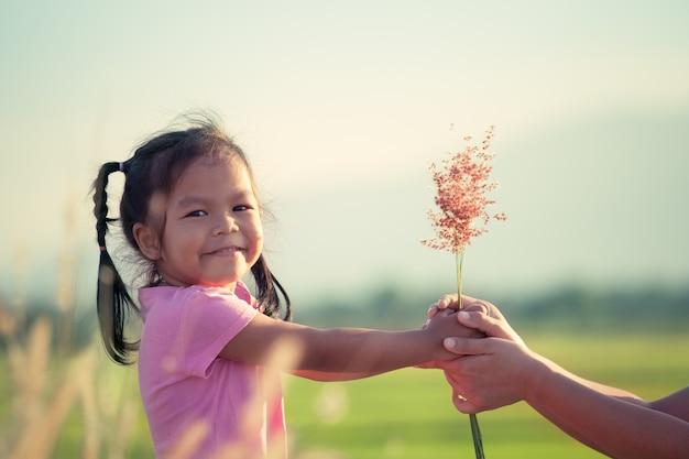 Ребенка азиатских девочка, давая траве цветок ее мать с любовью в старинный оттенок