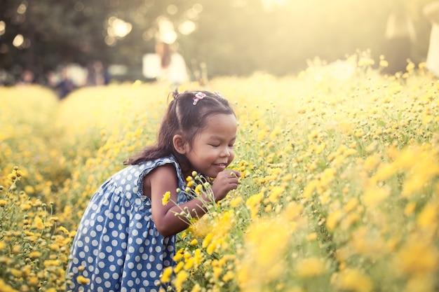 Ребенка азии девочка, пахнущие цветок в саду, с удовольствием с желтым полем цветок