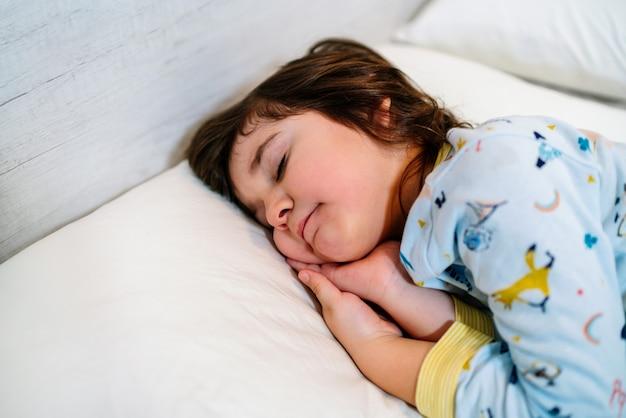 잠옷과 하얀 시트를 입고 눈을 감고 순진한 얼굴로 침대에서 잠자는 아이