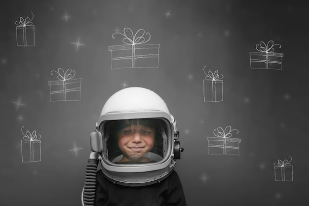 Child in an astronaut's helmet dreams of christmas and presents