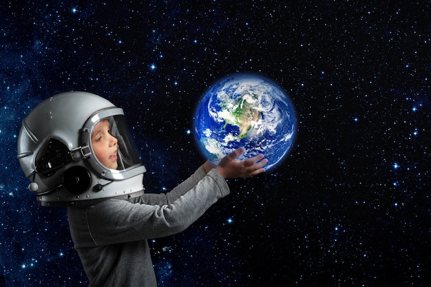 A child in an astronaut's helmet holds the earth in his hands