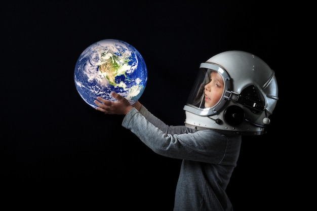 Child in an astronaut's helmet holds the earth in his hands