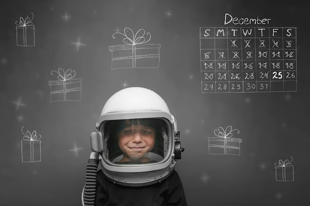 A child in an astronauts helmet dreams of christmas and presents