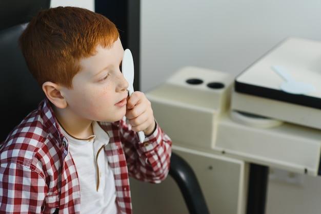 Тест на зрение ребенка. маленький ребенок, выбирая очки в магазине оптики.