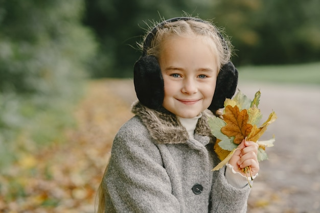 Child in a autumn park. kid in a gray coat.