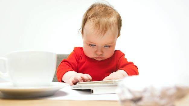 Ребенок девочка сидит с клавиатурой современного компьютера или ноутбука в белой студии.