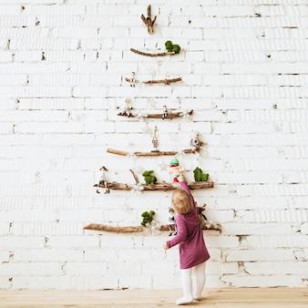 装飾されたミニマルでモダンなトレンディなクリスマスツリーにクリスマスのおもちゃに触れる子供の赤ちゃん