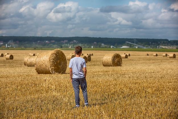 Child and bales of hay on the field.
