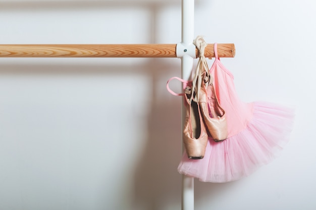 Child ballet dress and ballet shoes holding on a ballet barre. dance concept.