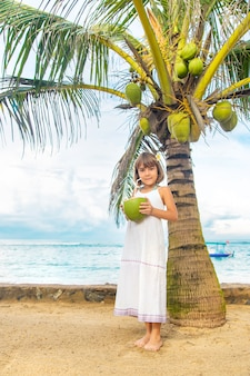 A child on the beach drinks coconut.