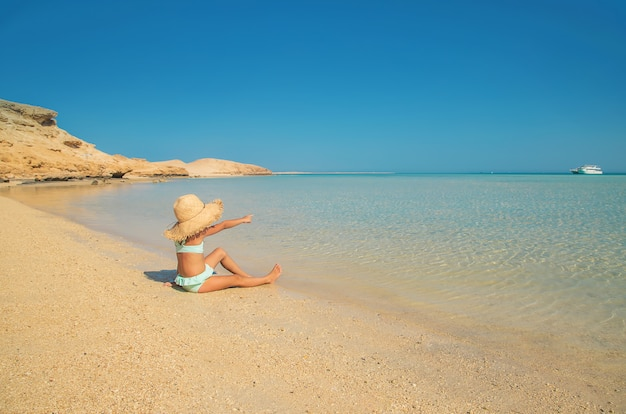 A child on the beach near the sea.
