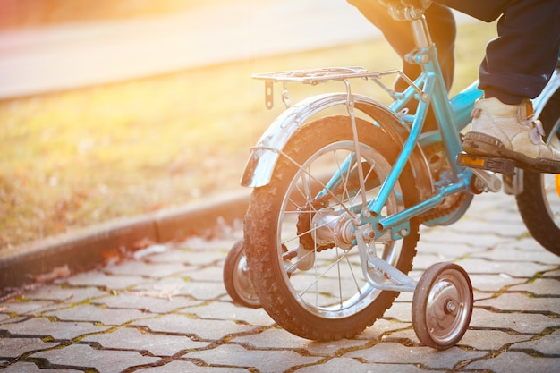 Child on a bicycle in sunny day. back view.