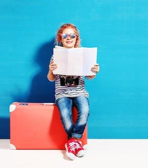 핑크 빈티지 가방 및 여름 휴가를위한 준비 도시지도와 자식 금발 소녀. 여행 및 모험 개념.
