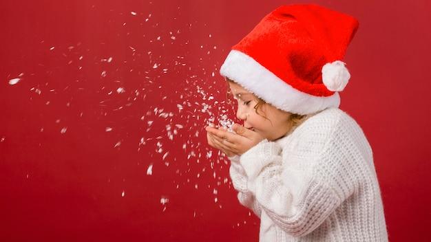 クリスマスの紙吹雪を吹く子供