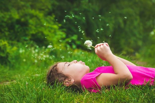 Ребенок дует одуванчики в природе. выборочный фокус. природа.