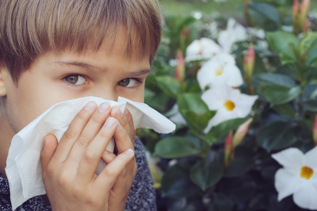 Child blowing his nose near blossoming flowers