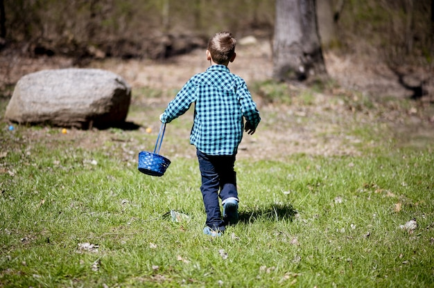 Child in a blue flannel shirt holding a basket and walking through a field under the sunlight