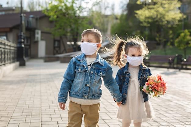 子供の男の子と女の子のフェイスマスク保護で野外を歩いています。コロナウイルス、covid-19