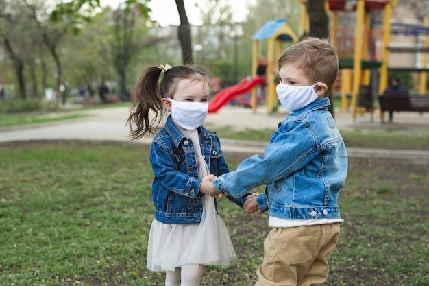 Мальчик и девушка ребенка гуляя outdoors с предохранением от лицевого щитка гермошлема. коронавирус (covid-19