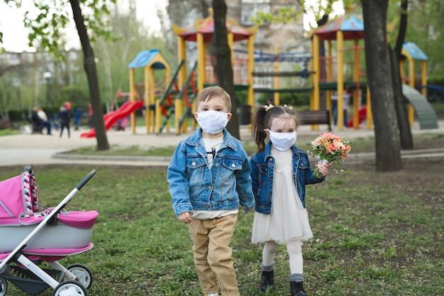 얼굴 마스크 보호와 함께 야외에서 걷는 어린 소년과 소녀. 코로나 바이러스 (코로나 19