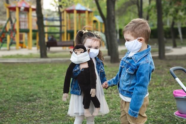 Мальчик и девушка ребенка гуляя outdoors с предохранением от лицевого щитка гермошлема. маленькая девочка держит чучело обезьяны в ее руках. коронавирус (covid-19