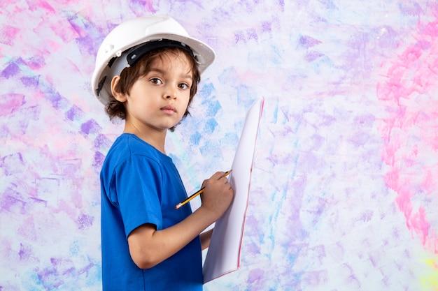 Ragazzo del bambino in maglietta blu piano di scrittura della carta in maglietta blu e casco bianco su colorato
