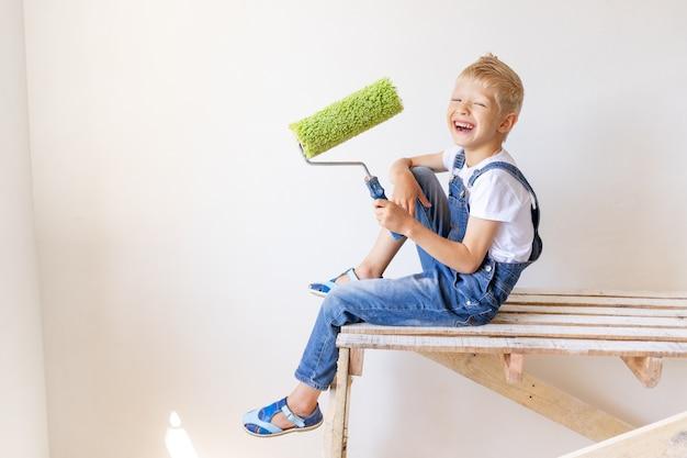 Ребенок мальчик строитель держит строительные инструменты в квартире с белыми стенами