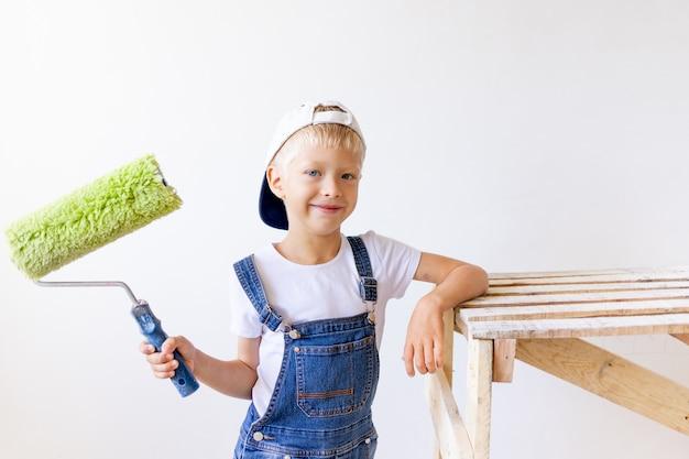 Ребенок мальчик строитель делает ремонт в квартире с белыми стенами, рабочий хочет покрасить стены валиком, место для текста
